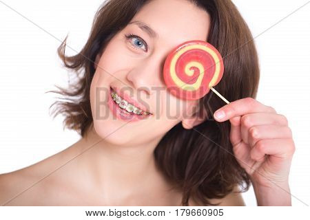 Young woman with multi-colored bracket system and candy. Dental concept
