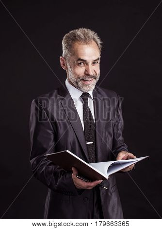 businessman with pen and papers ready for signature on a black background.the photo has a empty space for your text