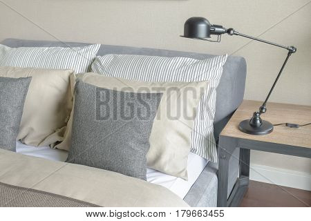 Brown Wall Bedroom With Pillows And Foldable Reading Lamp