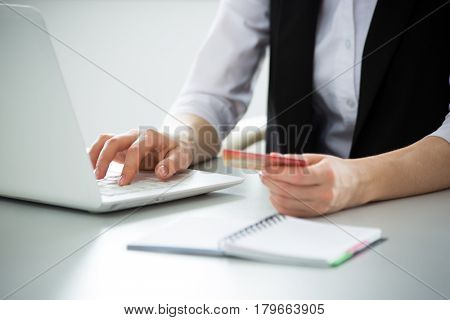 Businesswoman holding credit card and using laptop. Online payd.
