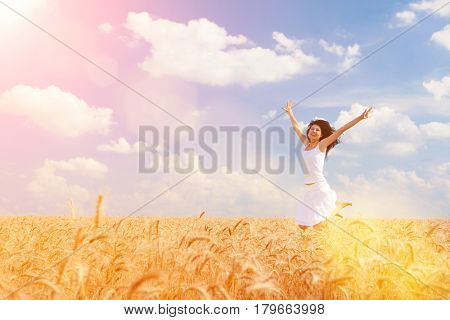 Happy woman jumping in golden wheat, enjoying the life in the field. Nature beauty, blue cloudy sky and field of wheat. Happy outdoor lifestyle. Freedom concept. Woman in summer field