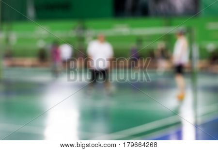 blurred of badminton court with players playing badminton