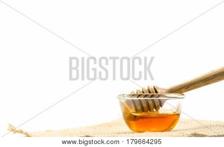 The Honey Dipper And Fragrant Honey Into A Transparent Bowl Isolated White Background.