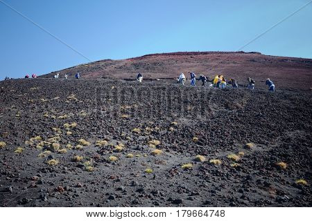 ETNA PARK, SICILY - MARCH 30, 2017: a group of tourists are climbing along a steep slope of volcanic ash of one of the hundreds of the craters in the Etna Park - Sicily