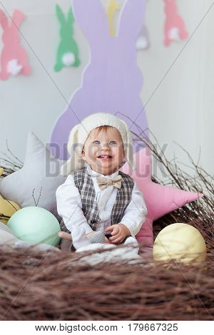 funny baby boy dressed in Easter bunny suit lying in a nest.