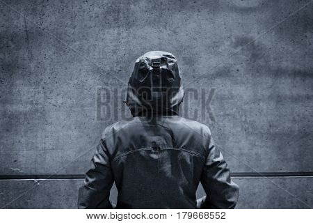 Unrecognizable hooded female person facing concrete wall as insurmountable obstacle young adult woman in urban surrounding confronting problems and difficulties in life.