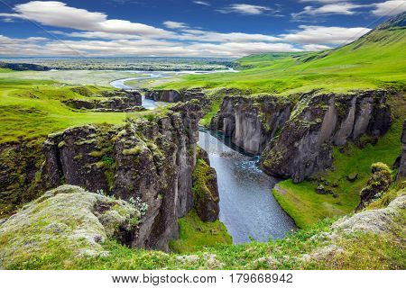 The striking canyon in Iceland. Bizarre shape of cliffs surround the stream with glacial water. The concept of active northern tourism