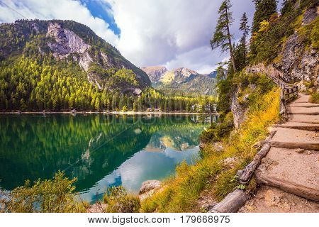 Magnificent Alpine lake Lago di Braies, Italy. Wide comfortable walking trail around the lake. The concept of environmental and hiking