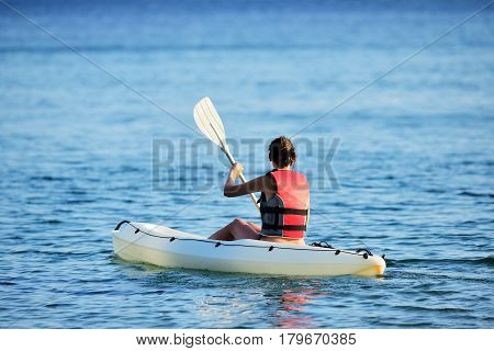 Cute young woman kayaking. Young lady in red life vest kayaking.