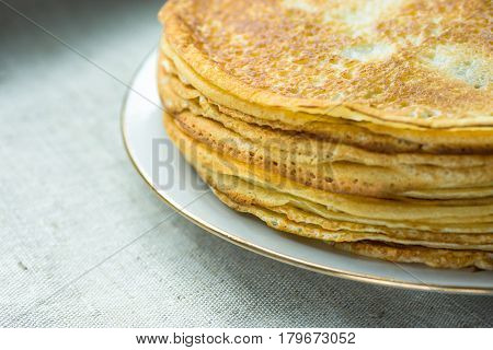 Stacked golden crepes on white plate on linen cloth background closeup breakfast cozy morning atmosphere