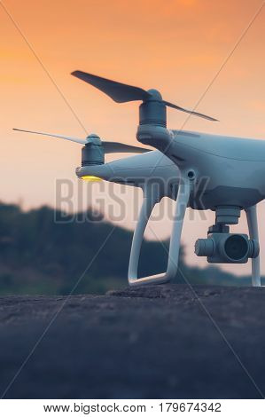 drone quad copter with digital camera at sunset ready to fly for surveillance. close-up of Rotor drones. Image has shallow depth of field. drone and remote. 4 blade propeller drone. Drone Video Camera. white color drone. Photos drones from Thailand. drone