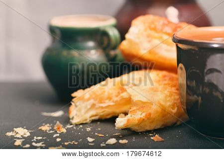 Ceramic ware and homemade rolls. Ware in rural style and fresh rolls from puff pastry are carelessly served on a gray background. Selective focus