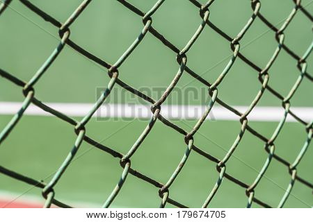 Close-up wire mesh steel with cort tennis background.