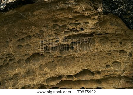 Close up of the texture of the big sandy cliff. Background of beige sand of sandy cliffs.