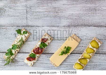 various crispbread slices on white woden kitchen table top view
