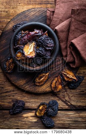 Prune dried plums fruits on dark rustic wooden background