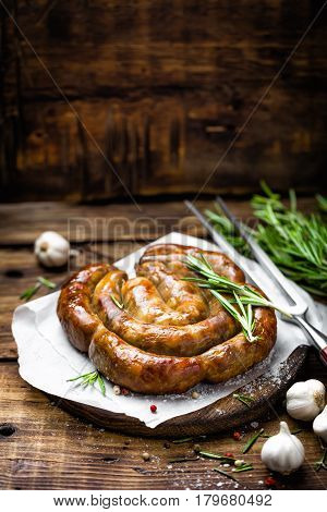 Grilled sausage on dark rustic wooden background