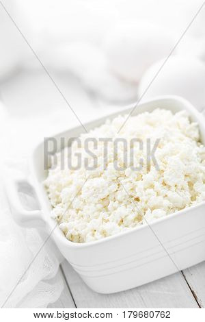 Cottage cheese on white wooden rustic background dairy product