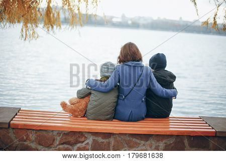 mother of two boys sitting on a bench near the river