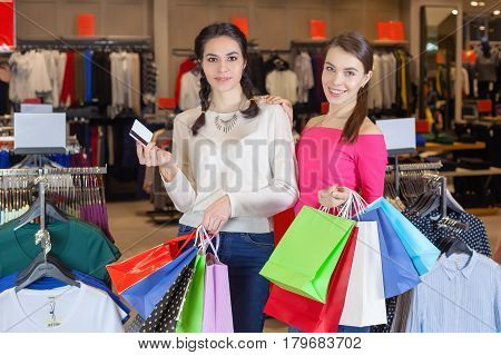 Two Beautiful Girls Make Themselves At The Mall With A Bag Of Gifts.