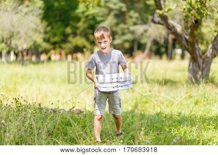 Small boy bringing three box of pizza for a picnic at the summer park