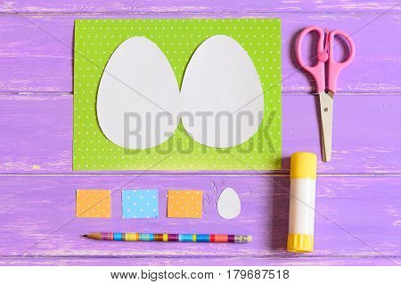 Creating Easter egg greeting card. Step. Guide. Colored paper sheets, templates in shape of egg, scissors, glue stick, pencil on a wooden table. Easy Easter craft idea for kids. Top view. Closeup