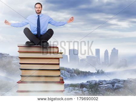 Digital composite of Businessman sitting meditating on Books stacked by distant city