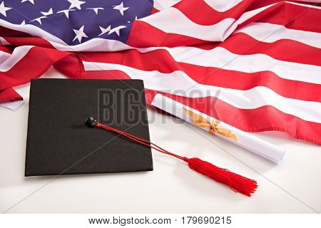 Close-up view of graduation mortarboard diploma and us flag on white education concept