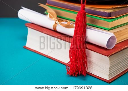 close up of book diploma and graduation cap with tassel on blue education concept