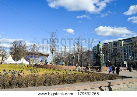 Moscow, Russia - March 23, 2017 - Pushkinskaya Square in the center of city with antique famous monument of russian poet Alexander Pushkin. Sunny spring day with walking people, houses, birds.