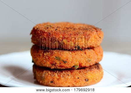 Veggie burgers on a plate. Healthy burgers prepared with carrots and herbs. Closeup