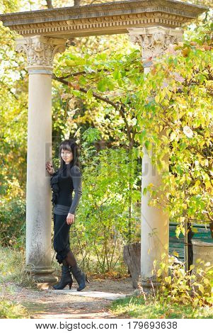 Pretty young woman in sunny park near ancient columns