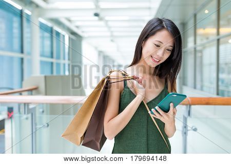Woman holding shopping bag and using cellphone for discount