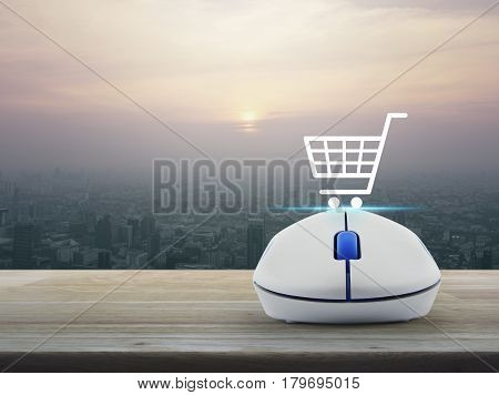 Shopping basket icon with wireless computer mouse on wooden table over modern city tower at sunset vintage style Shop online concept