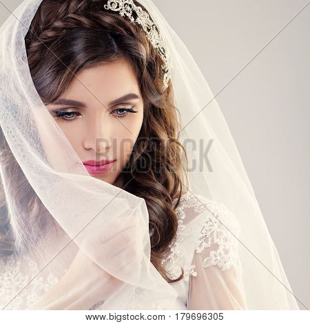Fashion Portrait of Perfect Bride. Beautiful Fiancee with Curly Hair Makeup and White Veil