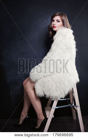 Beautiful Woman Fashion Model with Perfect Bob Hairstyle and Make up wearing White Fur Coat