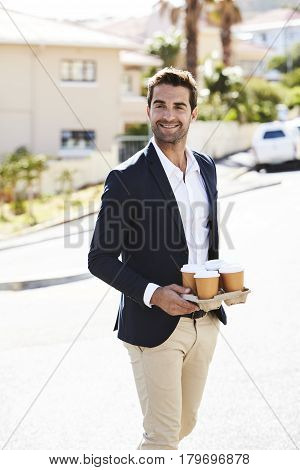 Man holding tray of coffee in street smiling