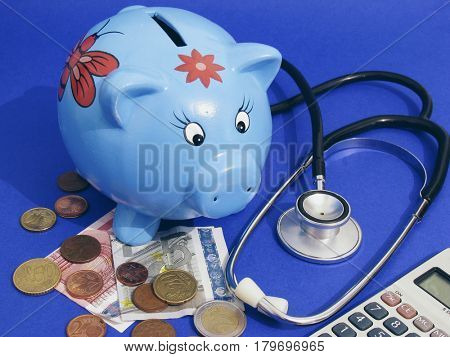 high coast of health, piggy bank and stethoscope and money
