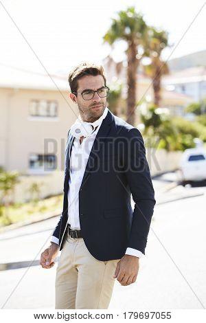 Dude with headphones in street looking away