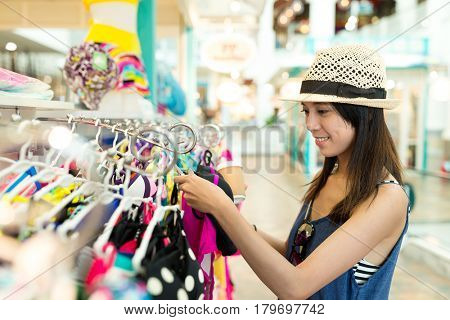 Woman choosing clothes in department store