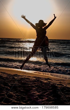 An attractive girl jumping happily out of the sunlit sea