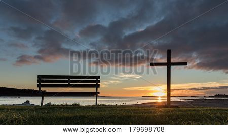 One park seat and one black cross at sunset.