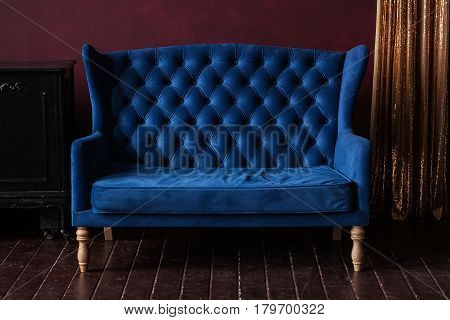 Marsala wall, golden curtain and vintage upholstered blue sofa.