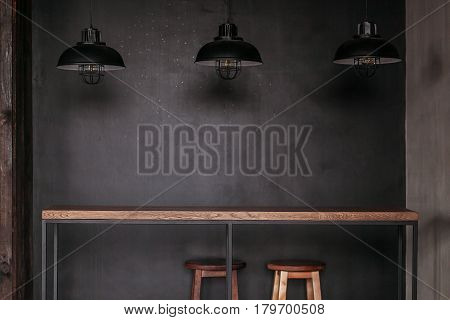 Dinning table set in loft style dining room with black lamps.