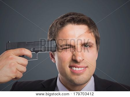 Digital composite of Close up of business man with gun to head against grey background