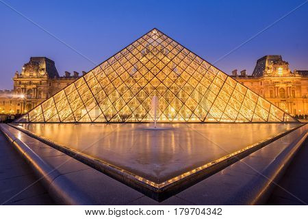 PARIS, FRANCE- March 21, 2015:  The large glass pyramid of the Louvre Museum in the evening on march 21, 2015. The Louvre Museum is one of the largest museums of the world