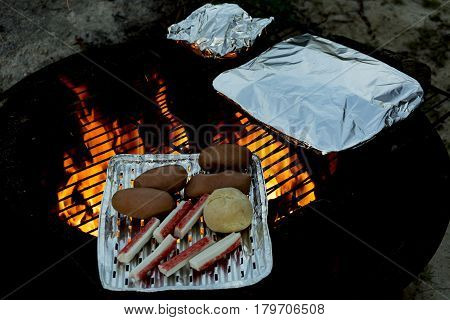 Start of broiling season. Start of grill season. Spring evening grill. Grilled lard sausages, crab bars, roll.
