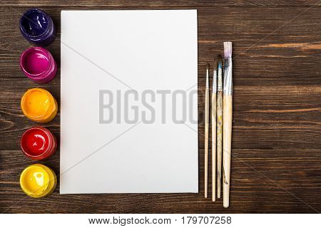 Artist's workshop. Top view of paintbrushes palette and acrylic paints with white canvas. Set of brushes and oil paints. Art picture with copy space and for add text.Items for children's creativity