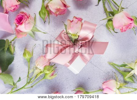 Gift box with pink satin bow and rose flowers