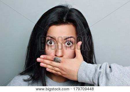 Young Woman In Gray Sweatshirt Shocked Or Surpised Covers Mouth With Hand On A Gray Background